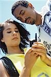 Couple using cell phone, low angle view Stock Photo - Premium Royalty-Free, Artist: Steve Prezant, Code: 695-03379245