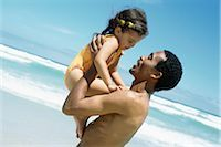 Man holding up daughter on beach, side view Stock Photo - Premium Royalty-Freenull, Code: 695-03379253