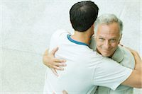 Man embracing adult son, smiling at camera, high angle view Stock Photo - Premium Royalty-Freenull, Code: 695-03379429