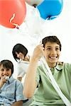 Boy holding helium balloons, smiling, mother and brother in background Stock Photo - Premium Royalty-Free, Artist: Glowimages               , Code: 695-03379665
