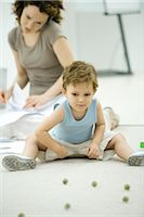 Boy playing with marbles while young mother uses phone and looks at paperwork in background Stock Photo - Premium Royalty-Freenull, Code: 695-03379718