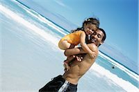 Father carrying daughter at the beach, both smiling at camera Stock Photo - Premium Royalty-Freenull, Code: 695-03379770