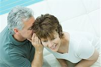 Woman looks away smiling as her husband whispers in her ear Stock Photo - Premium Royalty-Freenull, Code: 695-03380411
