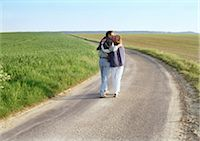 road landscape - Couple walking in road in between two green fields. Stock Photo - Premium Royalty-Free, Artist: Patrick Chatelain, Code: 695-03380972