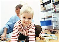 Young child facing camera in room with father Stock Photo - Premium Royalty-Freenull, Code: 695-03381008