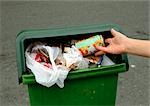 Person putting aluminum can into overflowing trash bin Stock Photo - Premium Royalty-Free, Artist: Science Faction, Code: 695-03381104