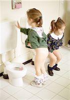 Two little girls using children's toilets Stock Photo - Premium Royalty-Freenull, Code: 695-03381153