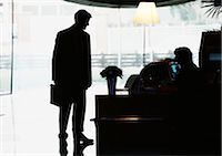 Silhouette of businessman standing by desk Stock Photo - Premium Royalty-Freenull, Code: 695-03381599