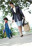 Businesswoman and child holding hands, walking, full length Stock Photo - Premium Royalty-Freenull, Code: 695-03381689
