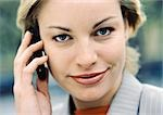 Businesswoman using cellular phone, looking at camera, close-up Stock Photo - Premium Royalty-Freenull, Code: 695-03382774