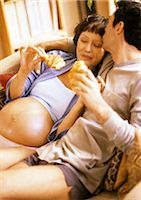 Man on sofa kissing pregnant woman, both holding croissants Stock Photo - Premium Royalty-Freenull, Code: 695-03384015