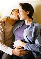 Pregnant woman sitting with arm around man, portrait Stock Photo - Premium Royalty-Freenull, Code: 695-03384040
