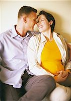 Man and pregnant woman sitting and smiling at each other Stock Photo - Premium Royalty-Freenull, Code: 695-03384049