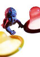 Plastic baby doll between condoms, close-up Stock Photo - Premium Royalty-Freenull, Code: 695-03384284