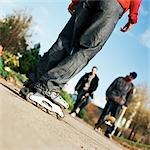 Young people, on wearing in-line skates, others with skateboards, low section Stock Photo - Premium Royalty-Free, Artist: Peter Griffith, Code: 695-03384709