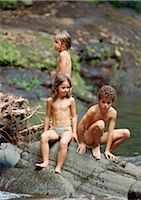 Boy and two girls in swimming trunks on a big rock, outside Stock Photo - Premium Royalty-Freenull, Code: 695-03385092