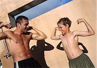 Man and boy flexing arm muscles, making faces. Stock Photo - Premium Royalty-Freenull, Code: 695-03385118