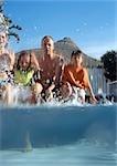 Family splashing at edge of pool, shot partially underwater