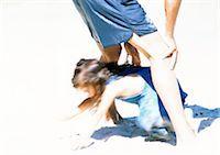 Girl crawling through man's legs on beach, blurred Stock Photo - Premium Royalty-Freenull, Code: 695-03385203