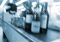Bottles on conveyor belt at checkout counter, blurred Stock Photo - Premium Royalty-Freenull, Code: 695-03385300