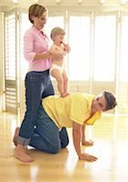 Man on all fours, woman holding baby on his back Stock Photo - Premium Royalty-Freenull, Code: 695-03385305
