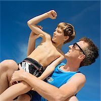 Father holding son, boy flexing arm, low angle view Stock Photo - Premium Royalty-Freenull, Code: 695-03385415