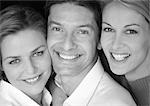 Two women and man side by side, smiling, close-up, portrait, b&w Stock Photo - Premium Royalty-Freenull, Code: 695-03385432