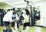 Woman standing next to man using exercise equipment in gym, laughing Stock Photo - Premium Royalty-Free, Artist: Masterfile, Code: 695-03385561