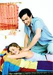 Woman lying on bed smiling, man giving her massage, looking into camera. Stock Photo - Premium Royalty-Free, Artist: Andy Lee, Code: 695-03385927