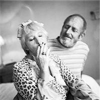 Mature couple sitting, woman smoking cigarette, b&w Stock Photo - Premium Royalty-Freenull, Code: 695-03385985