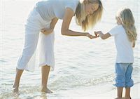 Mother holding hand out to girl on beach Stock Photo - Premium Royalty-Freenull, Code: 695-03388275