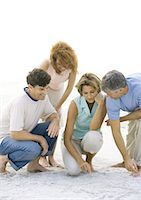 Two mature couples crouching on beach Stock Photo - Premium Royalty-Freenull, Code: 695-03388723