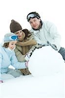 Three young friends making snowball, dressed in winter clothing, one looking at camera Stock Photo - Premium Royalty-Freenull, Code: 695-03389297