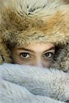 Preteen girl, wearing fur hat, looking over fur blanket, close-up Stock Photo - Premium Royalty-Freenull, Code: 695-03389318