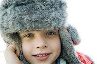Boy wearing fur hat, smiling at camera, close-up Stock Photo - Premium Royalty-Freenull, Code: 695-03389337