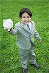 Little boy wearing full suit, holding up piggy bank, smiling at camera, full length Stock Photo - Premium Royalty-Free, Artist: ableimages, Code: 695-03389688