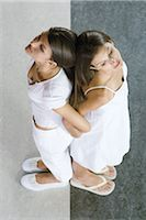 Twin sisters standing back to back, arm in arm, viewed from directly above Stock Photo - Premium Royalty-Freenull, Code: 695-03389706