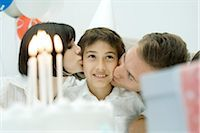 preteen kissing - Family behind birthday cake with lit candles, parents kissing boy on cheeks Stock Photo - Premium Royalty-Freenull, Code: 695-03389828