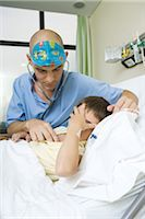 Boy lying in hospital bed holding head, doctor listening to boy with stethoscope Stock Photo - Premium Royalty-Freenull, Code: 696-03393973