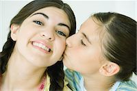 preteen kissing - Two young female friends, one kissing the other on the cheek Stock Photo - Premium Royalty-Freenull, Code: 696-03394064