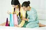 Two young female friends, one opening up gift bags