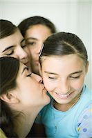 preteen kissing - Young female friends kissing younger girl's cheek Stock Photo - Premium Royalty-Freenull, Code: 696-03394076