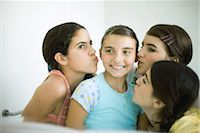 preteen kissing - Young female friends kissing younger girl's cheeks Stock Photo - Premium Royalty-Freenull, Code: 696-03394077