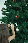 Girl decorating Christmas tree Stock Photo - Premium Royalty-Freenull, Code: 696-03394241