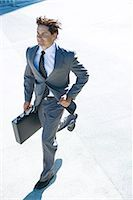 Young businessman running outdoors, carrying briefcase, smiling Stock Photo - Premium Royalty-Freenull, Code: 696-03394337