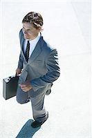 Young businessman walking outdoors, carrying briefcase, high angle view Stock Photo - Premium Royalty-Freenull, Code: 696-03394338