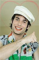Young man wearing lipstick, cap, and scarf, smiling at camera, portrait Stock Photo - Premium Royalty-Freenull, Code: 696-03394596