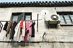 Laundry hanging out to dry below window, low angle view Stock Photo - Premium Royalty-Free, Artist: Transtock, Code: 696-03394748