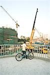 Man with bicycle looking at construction site, rear view Stock Photo - Premium Royalty-Free, Artist: Transtock, Code: 696-03395126