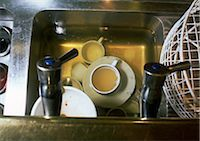 Dirty dishes soaking in water in sink, high angle view Stock Photo - Premium Royalty-Freenull, Code: 696-03396931